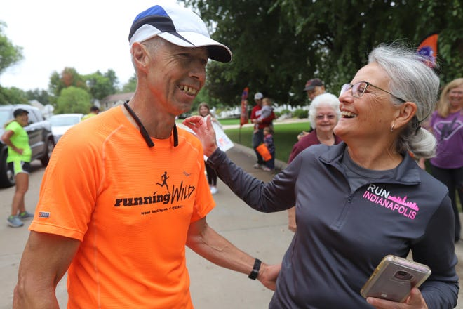 Richard Link, 60, of Burlington celebrates with his wife, Jean, after he finishes his virtual Boston Marathon Saturday in front of his home in Burlington.