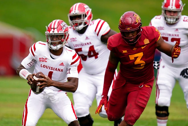 Louisiana-Lafayette quarterback Levi Lewis (1) runs from Iowa State defensive end JaQuan Bailey (3) during the game Saturday  in Ames.