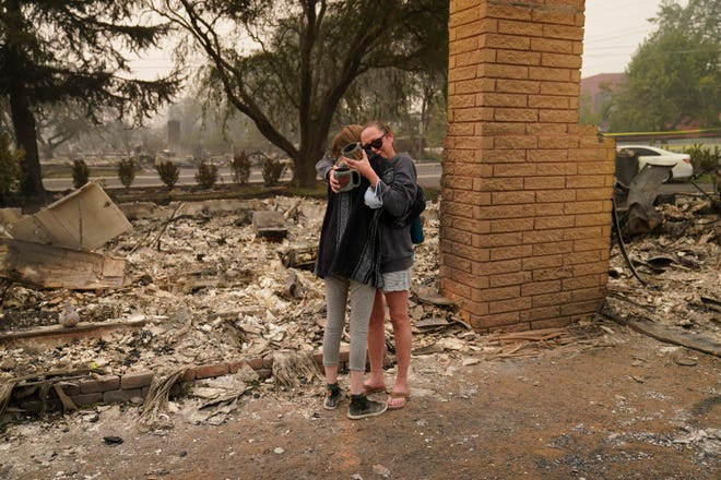 Desiree Pierce, right, hugs her stepdaughter Leah Johnson as they visit their home destroyed by the Almeda Fire on Friday in Talent, Ore.
