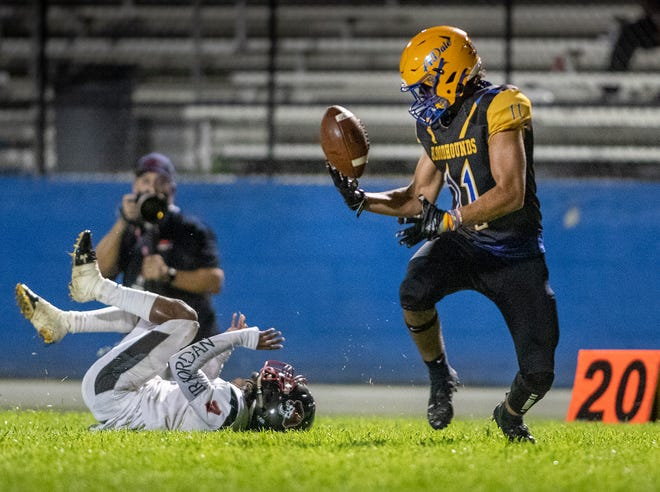 Auburndale's Jason Figley (11) tips the ball up in the air on a pass reception that he would run in for a touchdown as Pasco's Josiah Harrison (4) tries to defend during their game in Auburndale on Friday night.