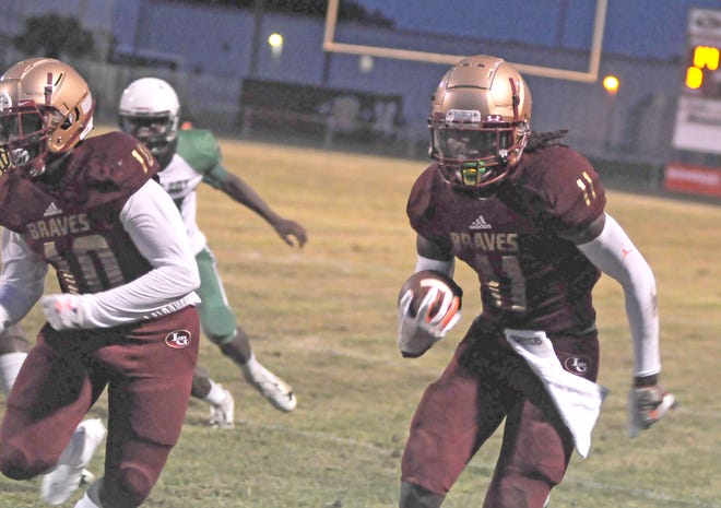 Lake Gibson's Sam McCall tightropes the sideline on a first-quarter punt return Friday against Haines City. McCall also returned the opening kickoff 80 yards for a touchdown and caught two more touchdown passes.
