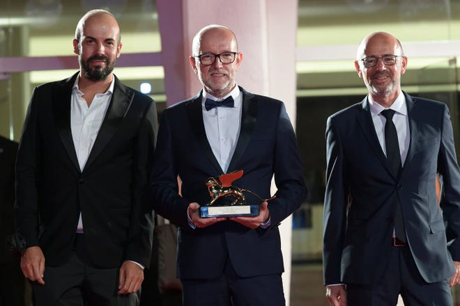 """Davide Romani, Disney's marketing director for Italy, center, holds the Golden Lion Best Film award for """"Nomadland,"""" at the closing ceremony Saturday of 77th edition of the Venice Film Festival in Venice, Italy. Director Chloe Zhao's """"Nomadland,"""" a recession-era road trip drama starring Frances McDormand, won the Golden Lion for best film at the Venice Film Festival, held against the backdrop of the coronavirus pandemic."""
