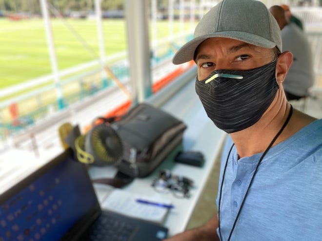 Palm Beach Post sports writer Joe Schad sits in the press box at the Dolphins' practice facility in Davie during this year's training camp while wearing his ever-present mask.
