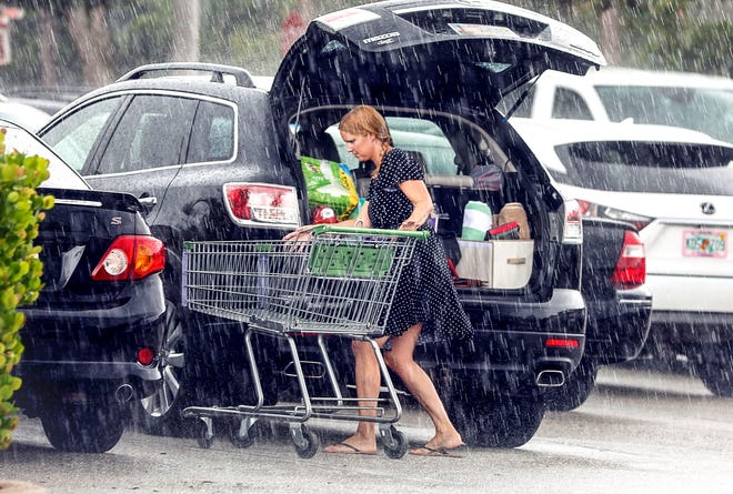 A woman gets drenched in a sudden downpour while trying to load her groceries into her car at the Chasewood Plaza Publix in Jupiter Saturday morning.