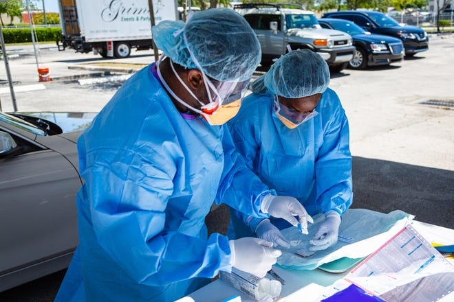 Medical assistants Nelson LaFrance, left, and Rosalyn James prepare a test kit May 4 at a coronavirus testing site at the St. John Missionary Baptist Church on Seacrest Boulevard in Boynton Beach.