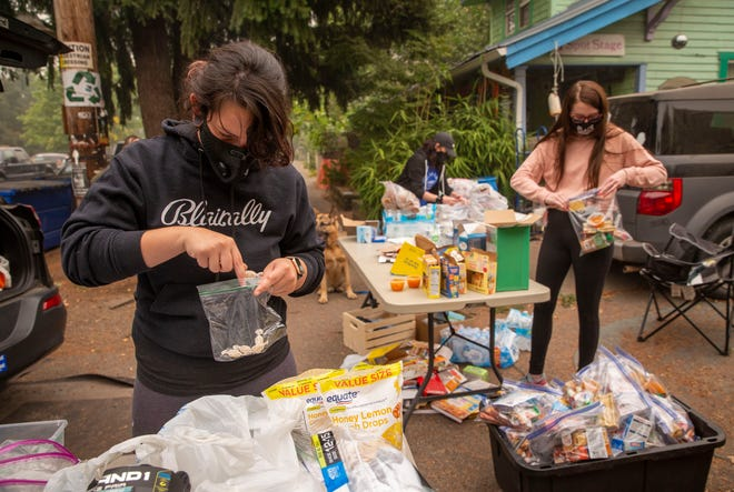 Black Unity supporters Amika Pass, Shawna Heurgue and Lauren Burnes pack bags to be distributed to unhoused people in Eugene on Saturday.