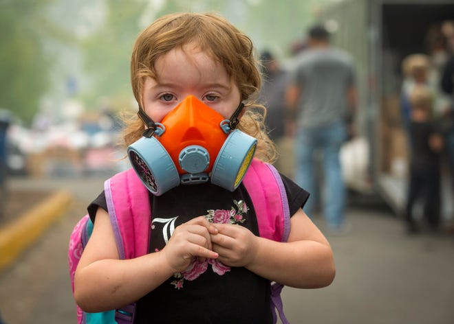 Kailiana Kroeker wears a respirator during a visit to donation site at Silke Field in Springfield, Oregon on September, 11, 2020. Air quality continued to be hazardous in the region due to smoke.