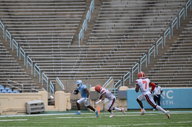North Carolina running back Michael Carter, left, scampers past Syracuse linebacker Geoff Cantin-Arku during Saturday's season opener at empty Kenan Stadium. [The Associated Press]