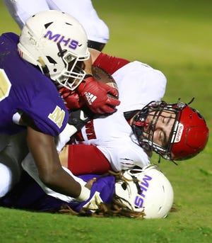 Blountstown's Garrett Martin (35) hangs onto the ball as he's tackled by Marianna's Johnny Curry (10) and Teqjuan Cuttino (5). Marianna faced off with Blountstown for a football game on Sept. 11, 2020.