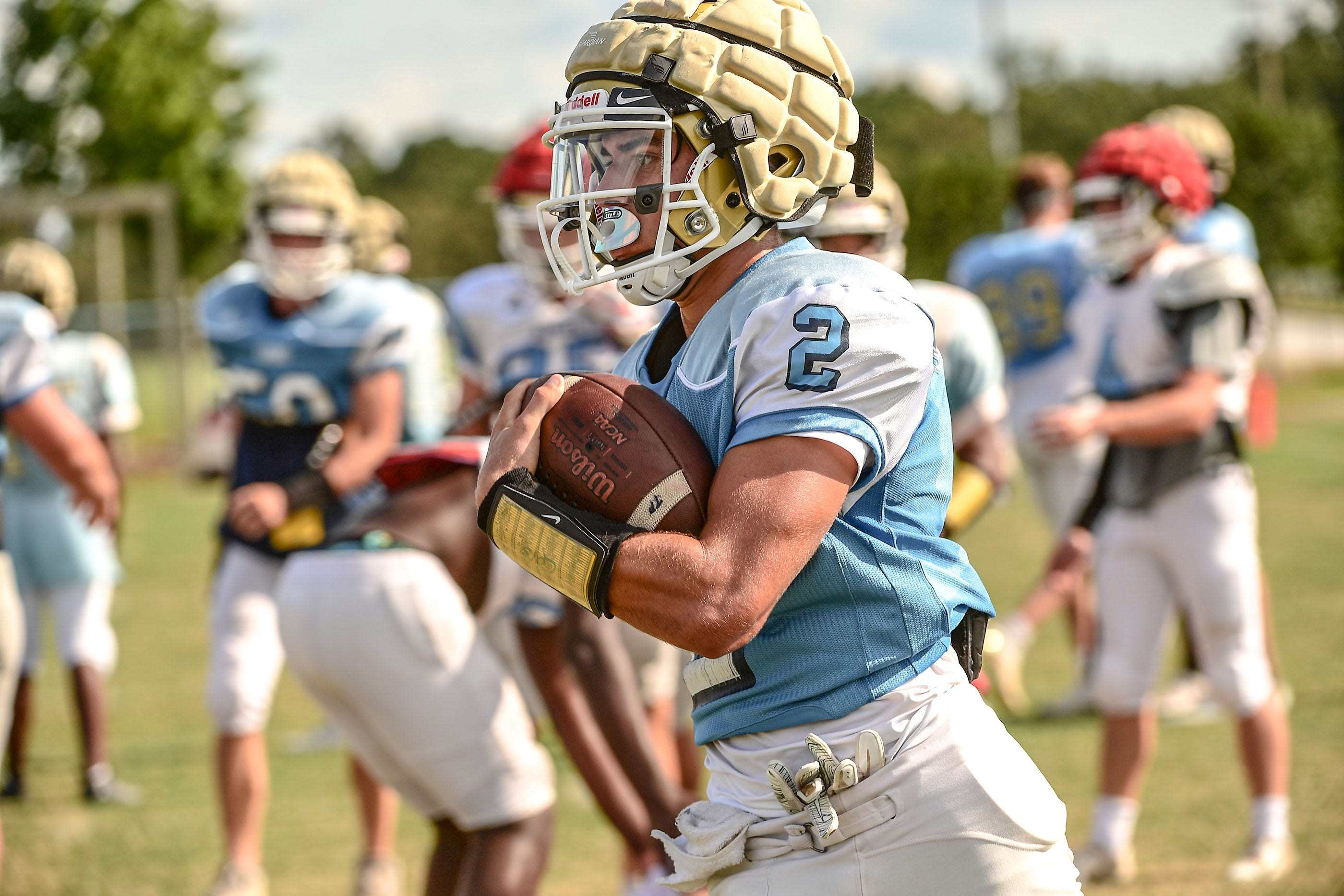 D.W. Daniel High School quarterback Jackson Crosby runs with the ball during practice in September 2020.
