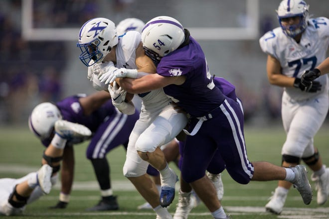 Elder linebacker Andrew Spinney (54) tackles St. Xavier wide receiver Liam Clifford (2) in the first half of the OHSAA regular season Division I football game between Elder and St. Xavier on Friday, Sept. 11, 2020, at The Pit in West Price Hill.