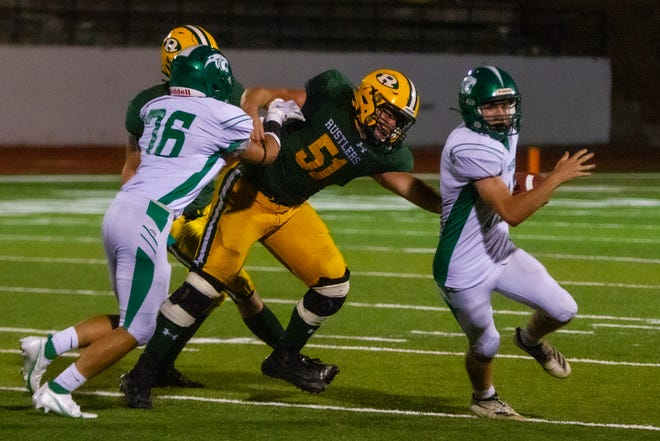 CM Russell senior Tyler Marr fights through a block to try and secure a tackle against Belgrade in the season opener Sept. 11 at Memorial Stadium. The Rustlers defeated the Panthers 27-0.