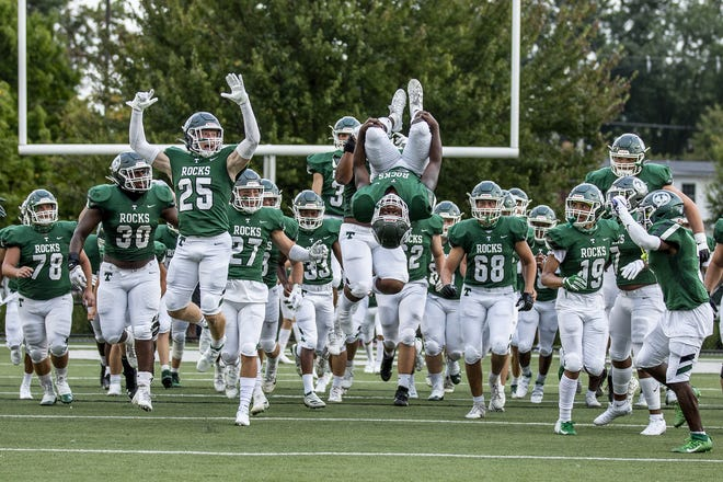 Trinity defensive back Roman White (21) went airborne for a backflip when the Shamrocks took the field before their game against visiting Cincinnati Moeller Friday night at Marshall Stadium. Sept. 11, 2020