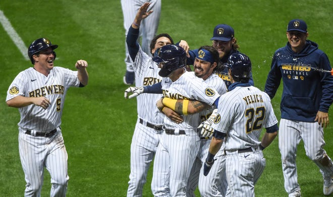 Ryan Braun is mobbed by Brewers teammates after his sacrifice fly drove in Christian Yelich in the ninth inning Friday night at Miller Park.