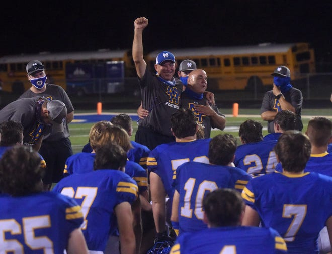 Mountain Home coaches Darin Acklin and Steve Ary celebrate while addressing the team after the Bombers' 41-7 victory over Nettleton on Friday night at Bomber Stadium. The victory snapped a 23-game losing streak for the program.