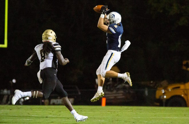 St. James' Cooper Wright (12) plucks a pass out of the sky as Bullock County's Robert Williams (8) gains on him.