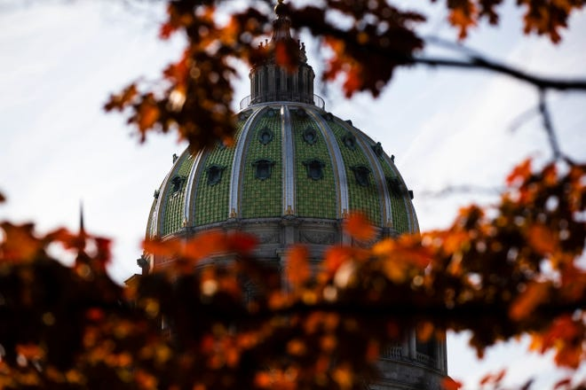 FILE- In this file photo from Nov. 19, 2019, the dome of the Pennsylvania Capitol is visible through the trees in Harrisburg, Pa. (AP Photo/Matt Rourke, File)