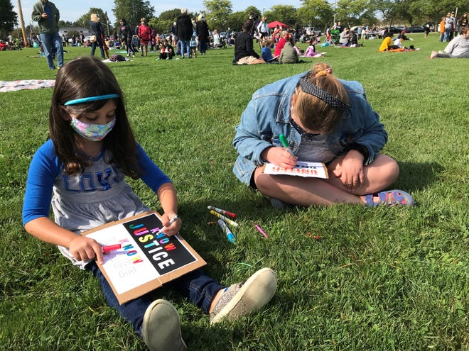 Evelyn Donolli, left, and Everleigh Stoffel decorate signs at a Black Kids Matter rally at Harris Whalen Park in Penfield.
