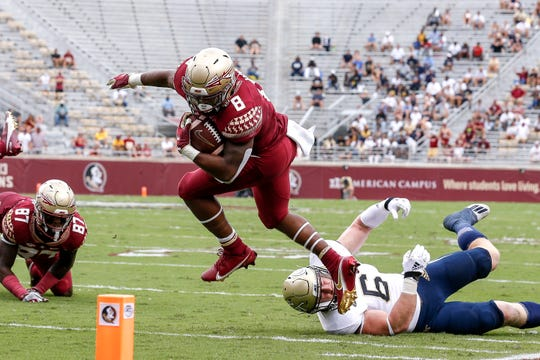 Florida State running back La'Damian Webb avoids a tackle by Georgia Tech linebacker David Curry during their game at Doak Campbell Stadium.