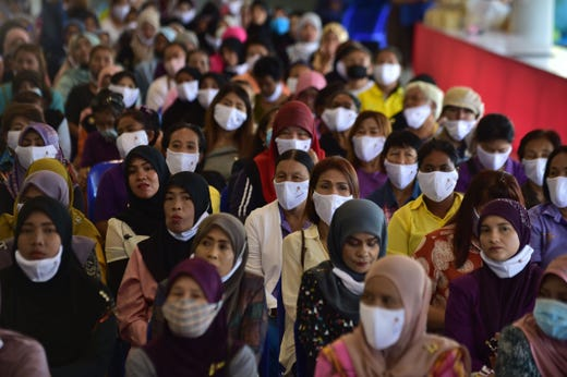 People wearing face masks attend a meeting by Thai government officials discussing the economic impact of the COVID-19 coronavirus in the border area with Malaysia at Sungai Kolok town in Thailand's southern province of Narathiwat on September 12, 2020.