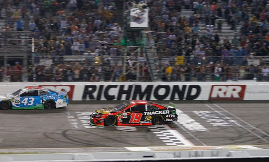 Martin Truex Jr. (19) takes the checkered flag to win the 2019 Federated Auto Parts 400 at Richmond Raceway.