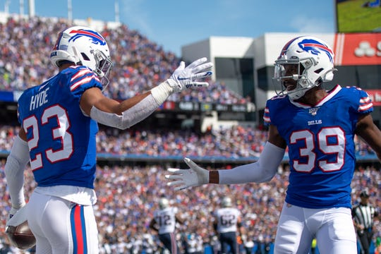 Buffalo Bills strong safety Micah Hyde (23) celebrates with teammate defensive back Levi Wallace (39) after his interception in the end zone during the second quarter against the New England Patriots at New Era Field.