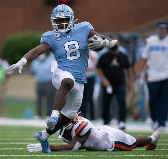 North Carolina's Michael Carter (8) breaks away from Syracuse's Ifeatu Melifonwu (2) for a gain of 20 yards in the first quarter of Saturday's 31-6 win.