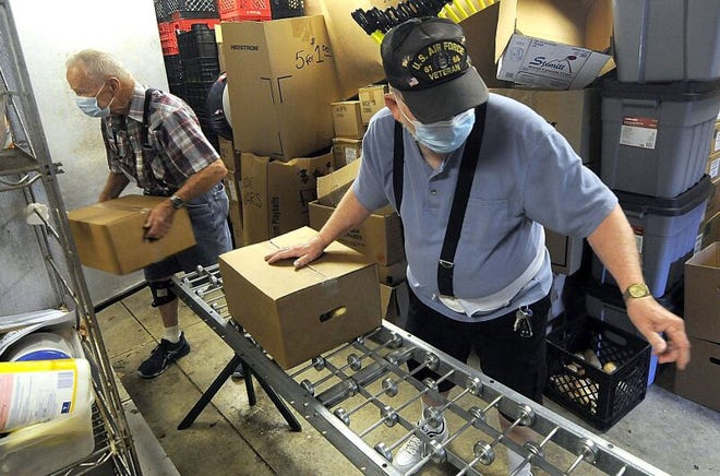 Ernie Cline, left, and Jim Belcher unload boxes of food into a walk-in refrigerator for the Hillsdale Cares ministry at Jeromesville Christian Church in Ashland County.
