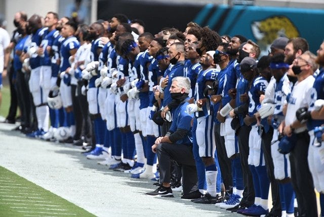 Indianapolis Colts players line up for the national anthem, with head coach Frank Reich kneeling, before their NFL football kickoff against the Jacksonville Jaguars at TIAA Bank Field on September 13, 2020. [Bob Self/Florida Times-Union]