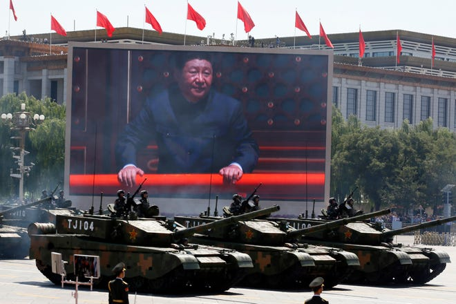 Chinese President Xi Jinping is displayed on a screen as Type 99A2 Chinese battle tanks take part in a September 2015 parade commemorating the 70th anniversary of Japan's surrender during World War II held in front of Tiananmen Gate in Beijing. China's Defense Ministry on Sunday blasted a critical U.S. report on the country's military ambitions, saying it is the U.S. instead that poses the biggest threat to the international order and world peace.