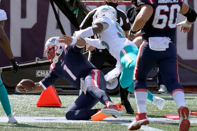 New England Patriots quarterback Cam Newton (1) scores his second rushing touchdown as Miami Dolphins linebacker Jerome Baker (55) chases in the second half Sunday in Foxborough, Mass.