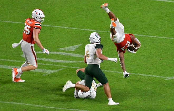 Hurricanes running back Cam'Ron Harris is flipped by UAB Blazers safety Grayson Cash during Miami's season opening victory Thursday. The Hurricanes jumped into the Top 25.