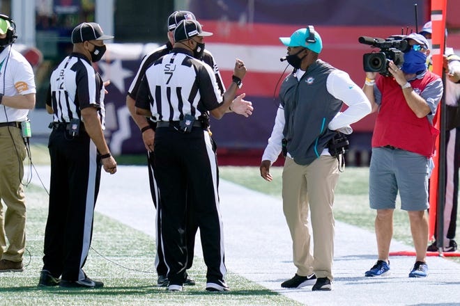 Miami Dolphins head coach Brian Flores, second from right, confers with officials in the first half of an NFL football game against the New England Patriots, Sunday, Sept. 13, 2020, in Foxborough, Mass. (AP Photo/Charles Krupa)