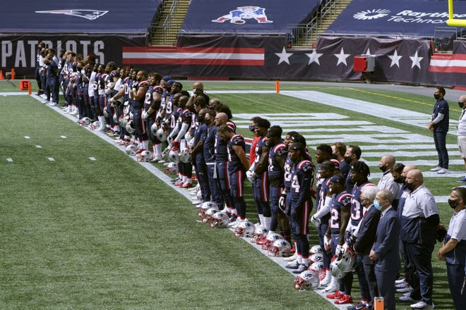 "New England Patriots stand during the singing of ""Lift Every Voice and Sing"" before the game against the Miami Dolphins on Sunday in Foxborough, Mass."