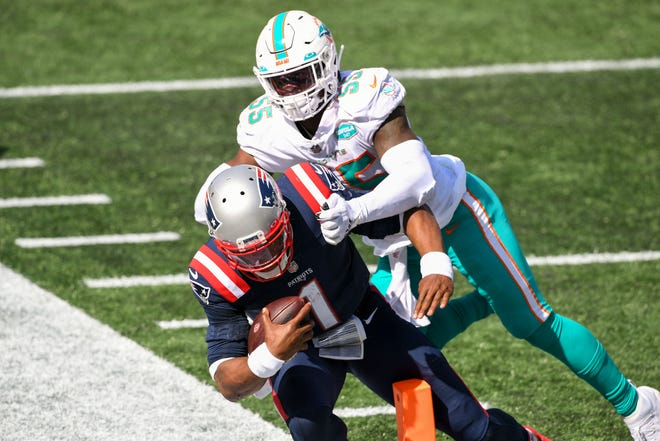 Patriots quarterback Cam Newton (1) dives into the end zone in front of Dolphins outside linebacker Jerome Baker during the third quarter Sunday.
