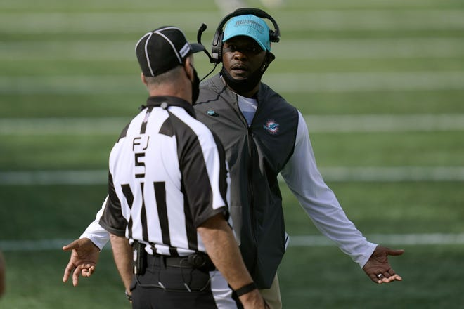 Dolphins coach Brian Flores appeals to field judge Jim Quirk.
