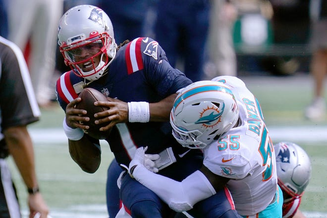 Miami Dolphins linebacker Jerome Baker (55) tackles New England Patriots quarterback Cam Newton.