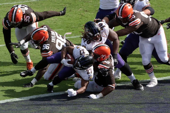 Baltimore Ravens running back J.K. Dobbins (27) breaks a Cleveland Browns linebacker B.J. Goodson (93) tackle for a second half touchdown   at M&T Bank Stadium.