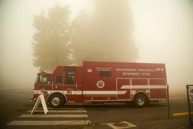 A Hazardous Materials Response Team truck heads into the foggy, smoky air from the Holiday Farm Fire incident command post at Thurston Middle School on Sunday, Sept. 13.