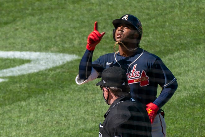 Atlanta Braves' Ozzie Albies, top, gestures as he rounds bases after hitting a two-run home run during the sixth inning of Sunday's game against the Nationals.
