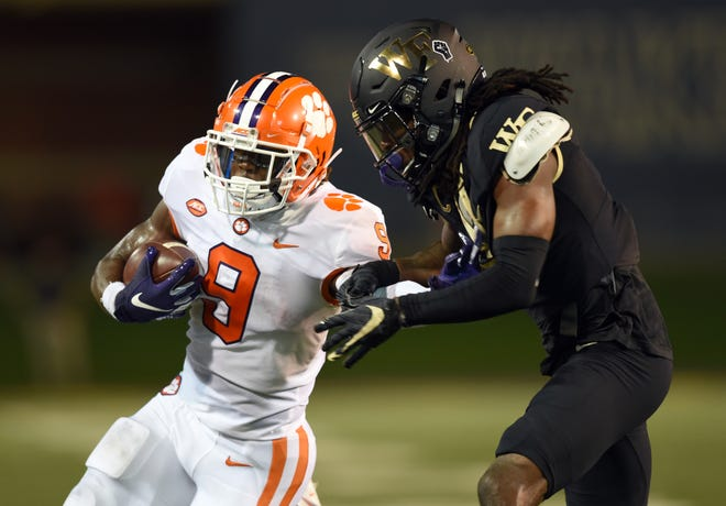 Clemson running back Travis Etienne tries to fend off Wake Forest's Ja'Sir Taylor on Saturday night.
