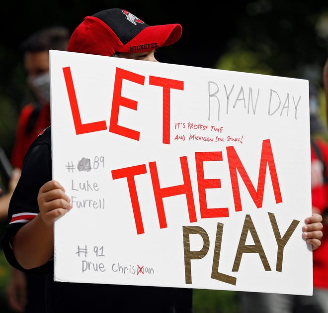 A young fan holds up a sign during a rally organized by parents of Ohio State football players outside the rotunda of Ohio Stadium in Columbus, Ohio on August 29, 2020.