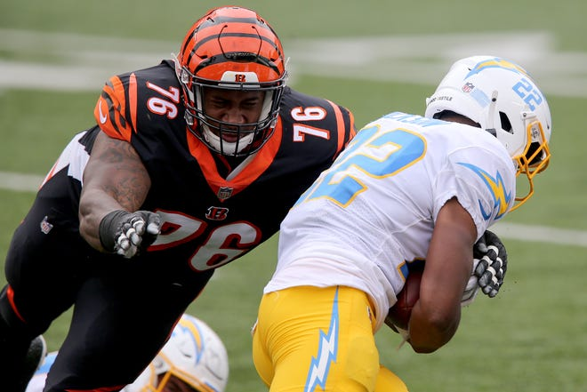 Cincinnati Bengals defensive tackle Mike Daniels (76) tackles Los Angeles Chargers running back Justin Jackson (22) in the first quarter during a Week 1 NFL football game against the Los Angeles Chargers, Sunday, Sept. 13, 2020, at Paul Brown Stadium in Cincinnati.