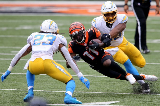 Cincinnati Bengals wide receiver John Ross (11) goes down after making a reception in the first quarter during a Week 1 NFL football game against the Los Angeles Chargers, Sunday, Sept. 13, 2020, at Paul Brown Stadium in Cincinnati.