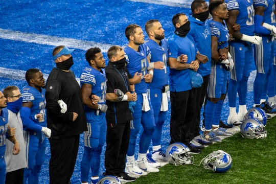 Detroit Lions players include quarterback Matthew Stafford, center, lock arms with each other as they watch a pregame presentation at the end zone before the season opener against the Chicago Bears.
