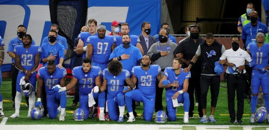 Lions players take a knee during the anthem before the first half at Ford Field.