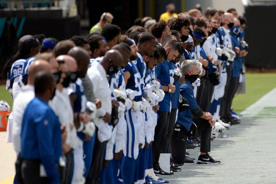 Indianapolis Colts head coach Frank Reich, center, kneels during the national anthem before the team's game against the Jacksonville Jaguars, Sunday, Sept. 13, 2020, in Jacksonville, Fla.