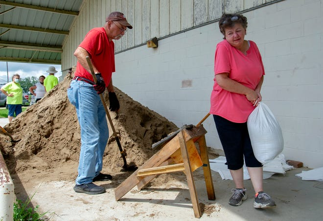 Mike and Arlene Stelly of Raceland team up to fill sandbags to protect their home. The couple were at the Raceland Agricultural Center on Texas Street Sunday, Sept. 13, 2020, in Raceland, La.