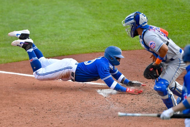 Toronto Blue Jays' Jonathan Villar, left, scores a run as New York Mets catcher Robinson Chirinos waits for the throw during the sixth inning of a baseball game in Buffalo, N.Y., Sunday, Sept. 13, 2020. (AP Photo/Adrian Kraus)