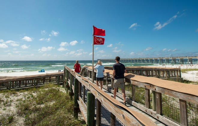 Double red flags, which means the  water is closed to the public, no swimming allowed, wave in the wind at Navarre Beach ahead of Tropical Storm Sally, Sunday, September 13, 2020.